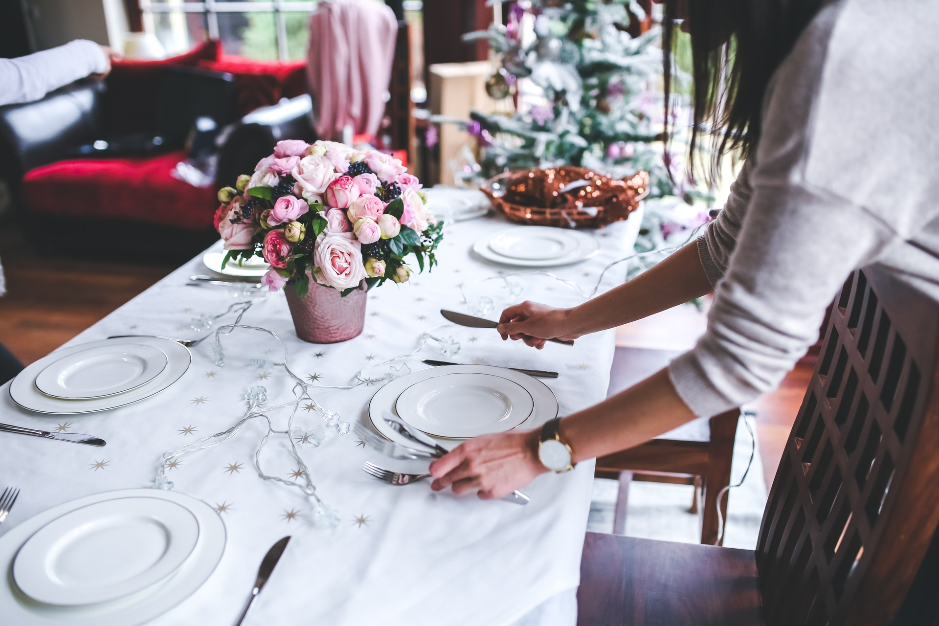 table with dishes being set by woman